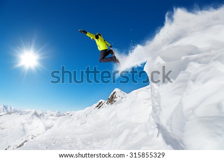 Jumping snowboarder at jump with alpine high mountains