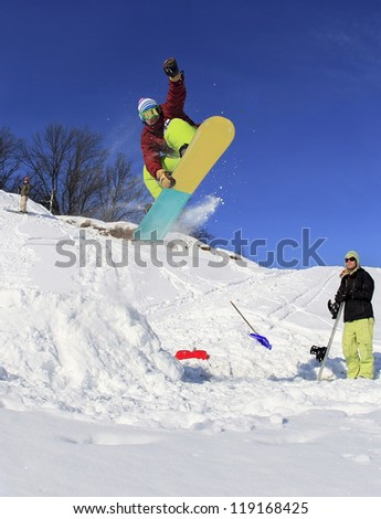 Jumping snowboarder in the mountains on blue sky background - stock photo