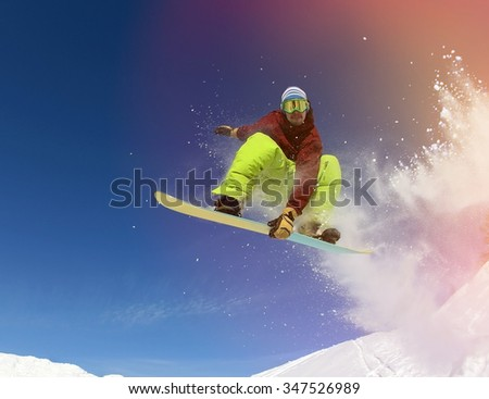 Jumping snowboarder keeps one hand on snowboard in mountains in ski resort on blue sky background - stock photo