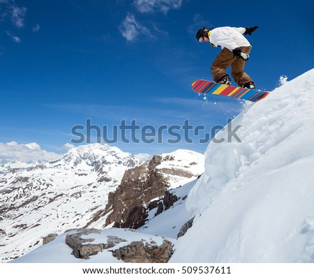 Jumping snowboarder keeps one hand on the snowboard on blue sky background