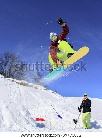 Jumping snowboarder keeps one hand on the snowboard on blue sky background - stock photo
