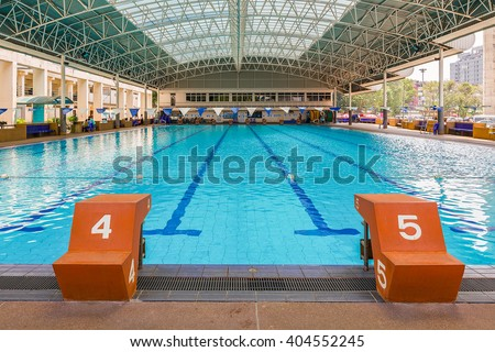 Jumping stand marked number four and five in front of swimming pool. - stock photo