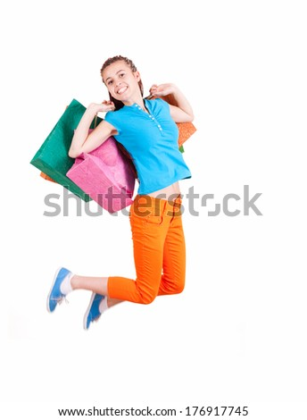 jumping teen girl holding shopping bags, white background - stock photo