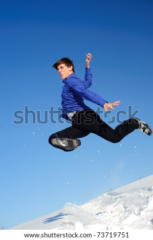 Jumping teenager in a cold day on snow field - stock photo