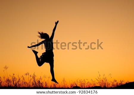 Jumping woman and sunset silhouett - stock photo