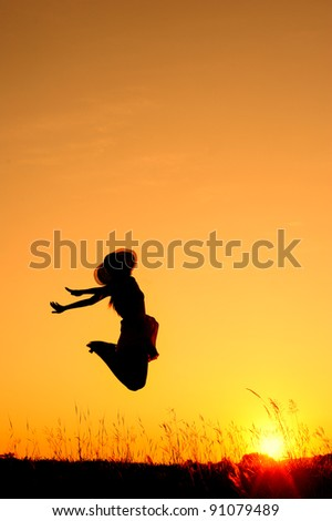 Jumping woman and sunset silhouette