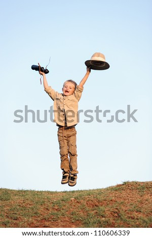 Jumping young child outdoors with binoculars and safari clothing and hat - stock photo