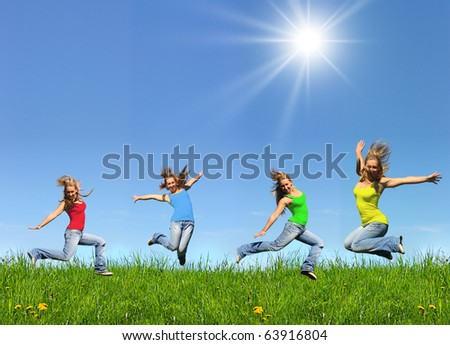 Jumping young girl in colorful clothes and blue jeans outdoors in a sunny day with place for your text. Perfect sky and green grass. - stock photo