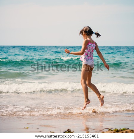 Jumping young girl on the beach portrait. - stock photo