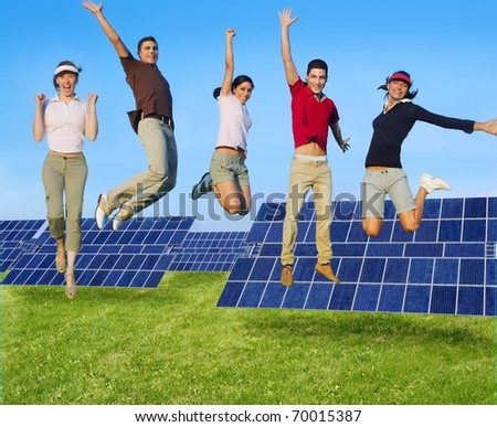 Jumping young people happy group green energy solar plates [Photo Illustration] - stock photo