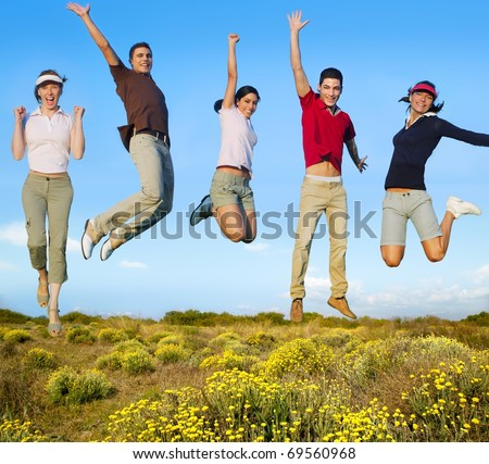 Jumping young people happy group in yellow flowers field [Photo Illustration] - stock photo