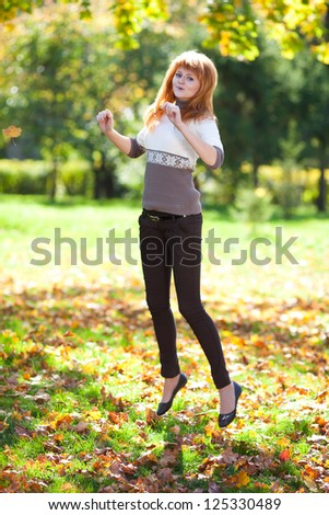 jumping young redhead teenager woman in the forest - stock photo