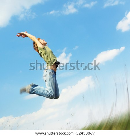Jumping young woman over blue sky background - stock photo