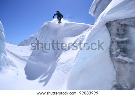 jumps skiers on the glacier - stock photo