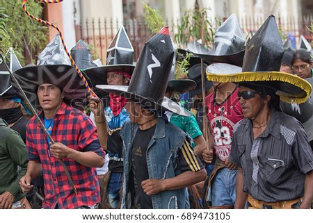 June 24, 2017 Cotacachi, Ecuador: indigenous kichwa men in costumes dancing on the street at Inti Raymi celebration