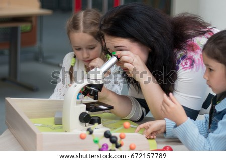 June, 2017. Minsk. Belarus. Museum of Science in the National Library. A woman and children look at the molecules in a microscope. STEM education.