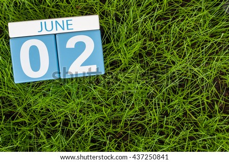 June 2nd. Image of june 2 wooden color calendar on green lawn grass background. Summer day.