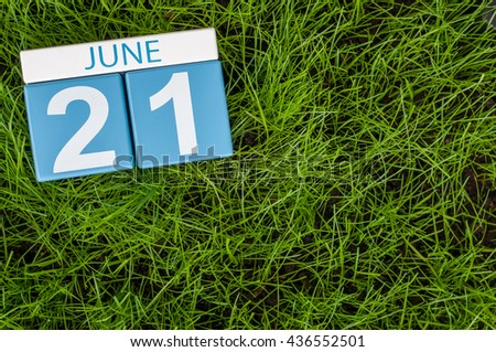 June 21st. Image of june 21 wooden color calendar on green grass lawn background. Summer day, empty space for text.