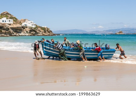 JUNE 8,2014-TANGIER, MOROCCO: Unidentified men pull a fishing boat to the beach.