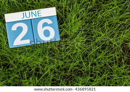 June 26th. Image of june 26 wooden color calendar on green grass lawn background. Summer day, empty space for text.