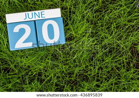June 20th. Image of june 20 wooden color calendar on green grass lawn background. Summer day, empty space for text.