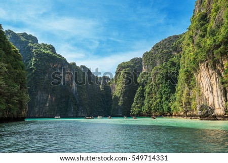 Jungle limestone cliffs around Phi-Phi Leh island with tourist boat parking
