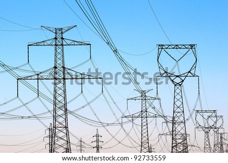 jungle of high voltage  power electricity pylons under sky - stock photo