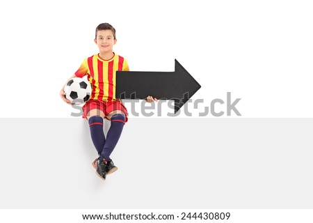 Junior athlete holding an arrow and a football seated on a bank signboard isolated on white background - stock photo