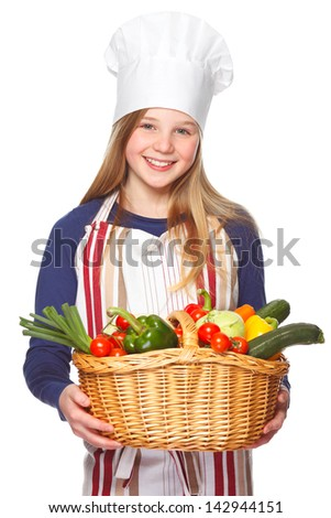 junior cook holding a basket full of vegetables - stock photo