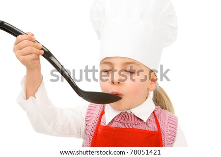 junior cook tasting something, spoon is empty for your own - stock photo