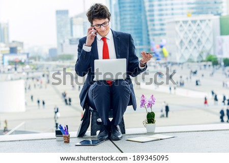 Junior executive dynamic leader phoning outside of his office - stock photo