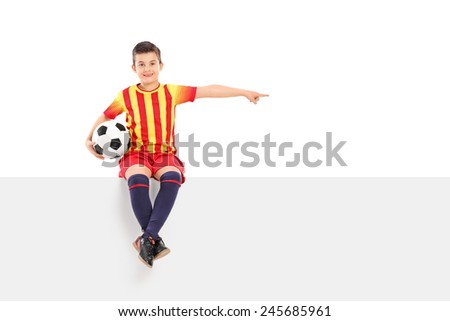 Junior football player pointing with his hand seated on panel isolated on white background - stock photo