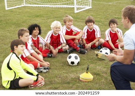 Junior football team training with coach - stock photo