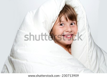 Junior girl covered white blanket isolated surprised happy face - stock photo