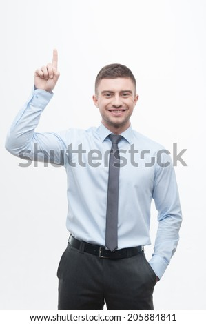 Junior handsome emotional manager in necktie showing process of idea search, pointing his finger up to empty space isolated on white - stock photo