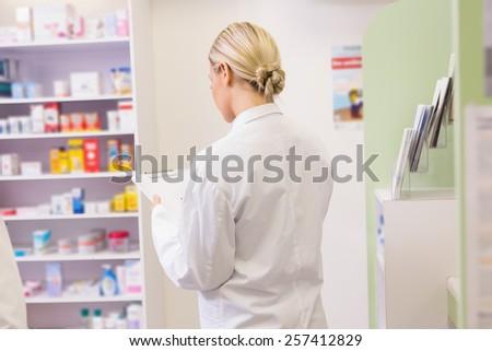 Junior pharmacist holding clipboard in the pharmacy - stock photo