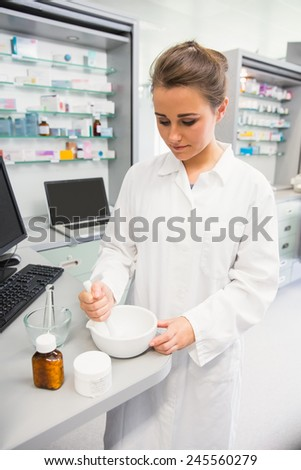 Junior pharmacist mixing a medicine at the hospital pharmacy - stock photo