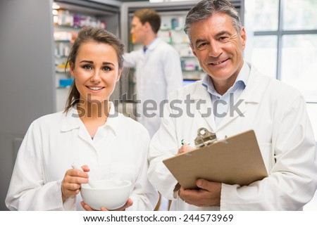 Junior pharmacist mixing a medicine with her senior at the hospital pharmacy - stock photo