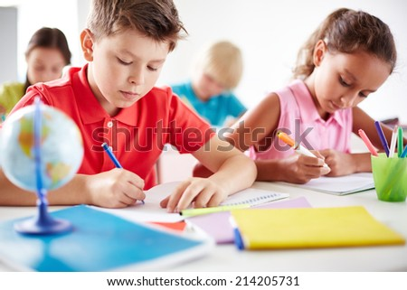 Junior pupils drawing with multi-color highlighters at lesson - stock photo