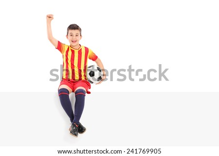 Junior soccer player gesturing joy seated on a panel isolated on white background - stock photo