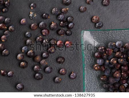 juniper berries macro detail closeup on black slate stone background - stock photo