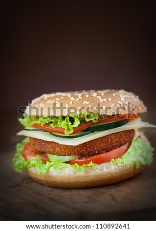 Junk food concept. Deep fried chicken or fish burger sandwich with lettuce, tomato, cheese and cucumber on wooden background.