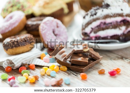 junk food, sweets and unhealthy eating concept - close up of chocolate pieces, jelly beans, glazed donuts and cake on wooden table - stock photo