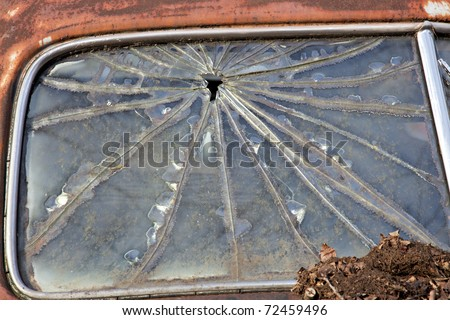 Junk yard car with broken window and rusted paint - stock photo
