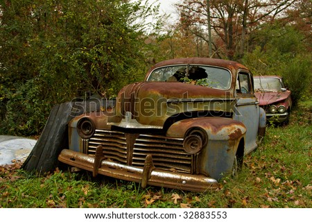 Junk yard vehicles showing old rusted car in overgrown weedy area - stock photo