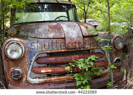 Junk yard vehicles showing old rusted truck  in overgrown weedy area - stock photo