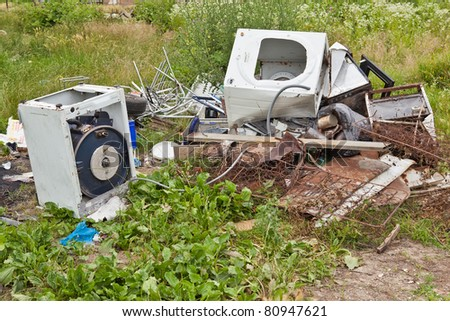 Junk yard with garbage scattered in the field - stock photo