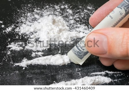 Junkie is snorting cocaine white powder with rolled banknote. Narcotics concept. - stock photo