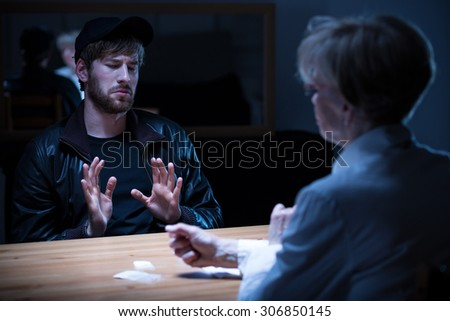 Junkie man interrogated by policewoman in a dark room - stock photo