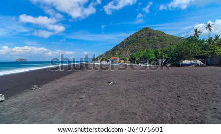 Junks on the beach of black sand on the island of Bali in Indonesia. Summer sunny day. - stock photo